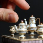 A curator examines a miniature tea set 1cm in height, made by Russian goldsmith Peter Carl Fabergé (Dominic Lipinski/PA Wire)