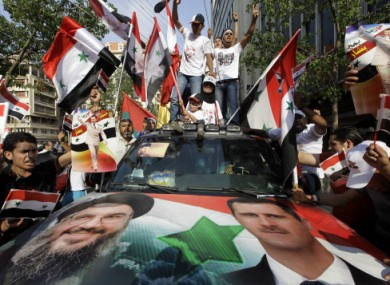 Syrian protesters carry flags and shout pro-government slogans during a rally outside the Syrian embassy in Beirut on 24 July 2011.