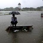 A security guard sits under an umbrella during monsoon rains in New Delhi, India. (AP Photo/Manish Swarup)