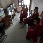 Young Buddhist monks play a virtual game of football at a video game parlor in Katmandu, Nepal. (AP Photo/Niranjan Shrestha)