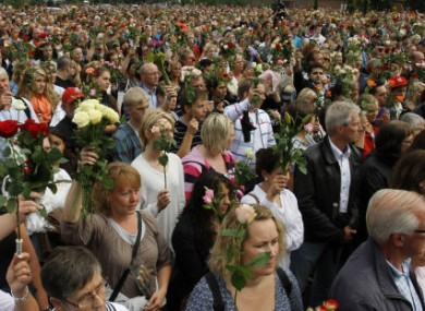 People hold up flowers during a vigil for the victims of the two attacks on Friday.