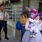 Conejta Pinta Caritas holds her daughter as they watch the Latin American Clown Congress parade in Guatemala City. (AP Photo/Rodrigo Abd)
