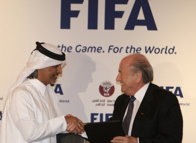 Blatter and the Qatari football president shake hands after Qatar are appointed as hosts of the 2022 World Cup.