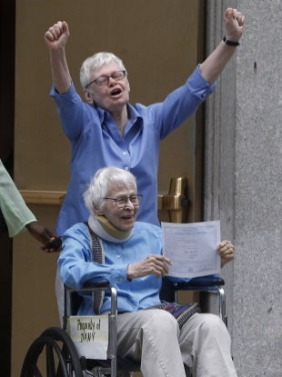 Phyllis Siegel, 76, and her wife Connie Kopelov, 84, (in wheelchair) celebrate becoming the first same-sex couple to be married at the Manhattan City Clerk's office yesterday