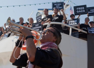 An activist plays a trumpet as others hold banners on their boat named