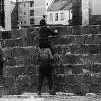 A boy sitting on the shoulders of another child peers over the wall just days after it was constructed. 