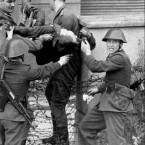 A dying man is carried away by the border guards who shot him on 17 August, 1962 as he tried to flee East Germany.  