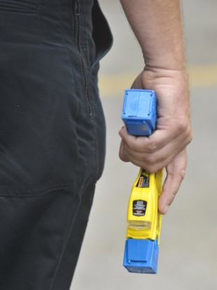 A police officer holds a Taser gun.