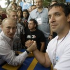 Putin prepares for arm wrestling during the Seliger youth educational forum visit. (AP Photo/Mikhail Metzel, Pool)