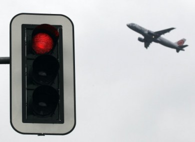 An aeroplane takes off behind a red traffic light at the international airport in Dusseldorf yesterday. An air traffic controllers' strike planned for tomorrow could wreak havoc on the travel plans of many.