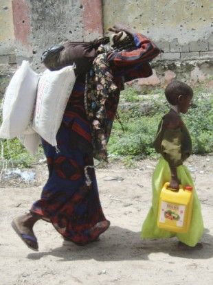 A Somali woman and her child carry food aid distributed by the Muslim Aid Organisation on 4 August 2011.