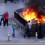 People pose for pictures near a burning car near Moor St Station and the Selfridges building in Birmingham, as fresh disturbances saw looting and vehicles set alight Birmingham.