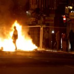 A rioter walks through a burning barricade on Smithdown Road in Liverpool, as around 200 missile-throwing youths gathered in the Toxteth area of Liverpool causing disorder and damage.