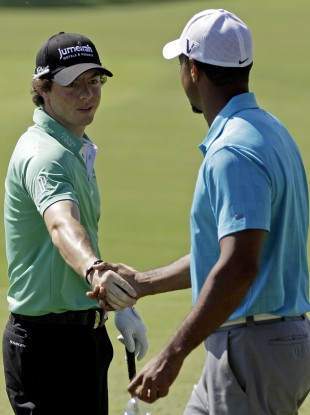 Rory McIlroy and Tiger Woods shake hands on the range at the PGA Championship golf tournament.