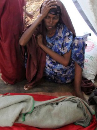 Amina Salah Ali sits by the body of her son who died at a Mogadishu camp on 10 August 2011.