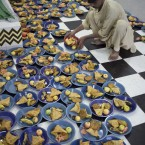 A volunteer arranges plates for people gathered to break their fast during Ramadan in Rawalpindi, Pakistan (AP Photo/B.K.Bangash)