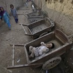A boy sleeps inside a wooden cart in a slum on the outskirts of Islamabad, Pakistan (AP Photo/Muhammed Muheisen)