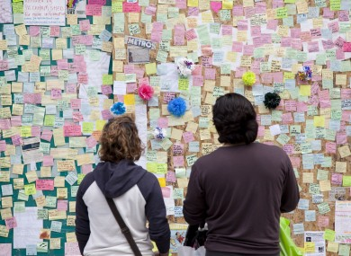 Notes are pinned up at a 'Peace Wall' on a boarded-up window of the Poundland store on Rye Lane, Peckham, which was destroyed during last week's riots.