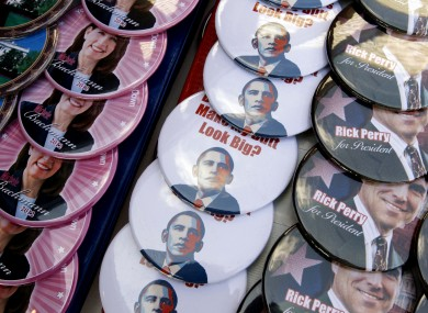 Some anti-Barack Obama badges are seen at a fair in Iowa, beside badges supporting Michele Bachmann and Rick Perry.