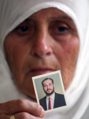 Wajeeha Allawi, 76, mother of Al-Jazeera reporter Samer Allawi poses with a photo of her son today.