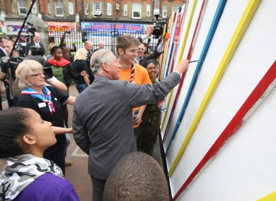 The Prince of Wales paints on a wall in Croydon as he and the Duchess of Cornwall visited the area blighted by the recent riots.