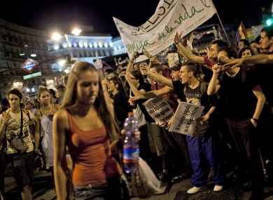 A Catholic pilgrim walks past shouting protesters in Madrid