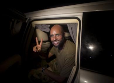 Muammar Gaddafi's son Seif al-Islam makes the victory sign as he appears at the Rixos hotel in Tripoli, Libya
