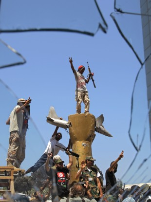 Rebels celebrate on top of a monument inside the Gaddafi compound.