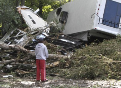 Lauren McTear looks over the remains of the trailer home owned by her boyfriend's parents today in Vermont.