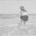 Two girls have their long skirts tucked up and are holding onto each other as they paddle in the sea.