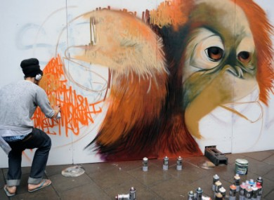 A graffiti artist at work in the See No Evil street art project in Bristol today.