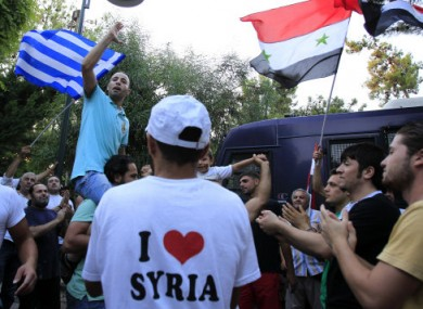 Syrians who live in Greece and Greek supporters shout slogans outside the Syrian embassy in Athens