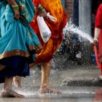 A woman splashes water to cool the feet of Hindu devotees arriving from different parts of Nepal in the holy 'Bol Bom' pilgrimage in Katmandu. (AP Photo/Niranjan Shrestha)