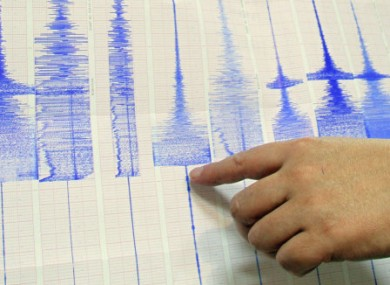 File photo: a seismologist points at a  Richter scale graph showing a 6.4-magnitude earthquake.