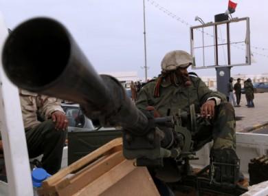 File photo: An anti-Gaddafi fighter sits with an anti-aircraft gun in Ras Lanouf on 5 March.