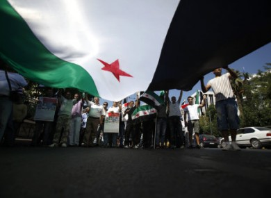 Syrians living in Greece raise up a huge Syrian flag during a protest in Athens against the suppression of protesters.