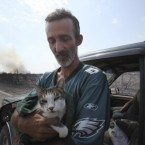 Mike Hester holds a cat he rescued from an area destroyed by a wildfire at Possum Kingdom Lake, Texas. (AP Photo/LM Otero)