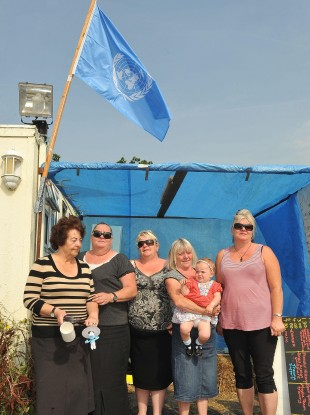 Members of the McCarthy family below a UN flag been flown at the Dale Farm site in Essex yesterday.