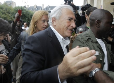 Dominique Strauss-Kahn and Anne Sinclair are crowded by media as they arrive back at their Parisian home.