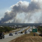 Large wildfires seen from a highway near Smithville, Texas. (AP Photo/Erich Schlegel)