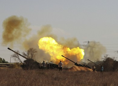 Libyan fighters fire canons toward pro-Gaddafi forces from the western outskirts of Sirte yesterday.