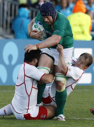 Russia's Valeriy Tsnobiladze, left, and Alexander Yanyushkin tackle Ireland's Sean O'Brien.