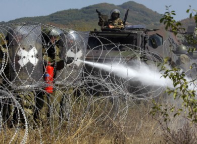 German troops of NATO's peacekeeping mission extinguish a fire along the border between Serbia and Kosovo yesterday.