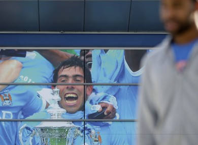 A fan passes a mural outside Manchester City's Etihad Stadium.