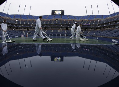 Workers clear water from the court at Arthur Ashe Stadium.