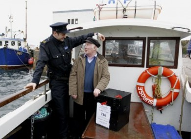File photo: Garda Ronan McNamara and presiding officer Hugh O'Donald bring a ballot box to Inishfree for the general election.