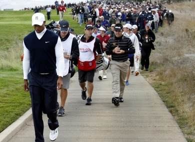 Tiger Woods leads the gallery down the second fairway during the first round of the Frys.Com Open golf tournament yesterday.