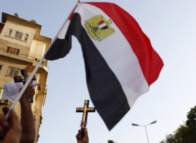 Egyptian Coptic demonstrators carry Christian crosses and an Egyptian flag during a Copts demonstration in Cairo