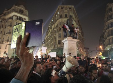 An Egyptian lifts the Muslim holy book, the Quran, as others light candles at Talat Harb square in downtown Cairo to mourn last week's attacks.