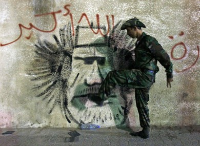 A former rebel soldier kicks an image of Gaddafi after news of his death emerged